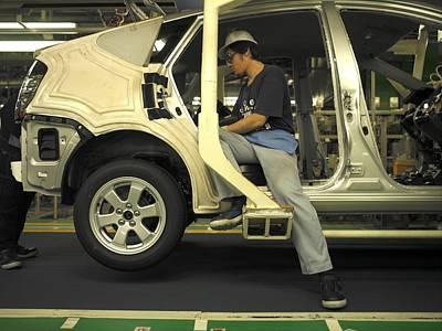 An Auto Worker Assembling A Toyota Poster