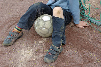 Boy With Soccer Ball Sitting On Dirty Field Poster