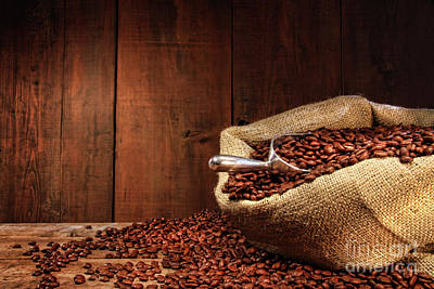 Burlap Sack Of Coffee Beans Against Dark Wood Poster by Sandra Cunningham