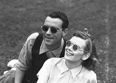 Couple Wearing Sunglasses Sitting On Grass, (b&w) Poster