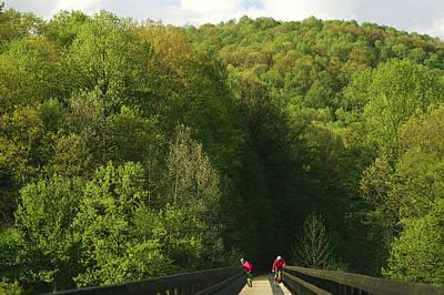Cyclists Cross A Bridge Poster by Joel Sartore