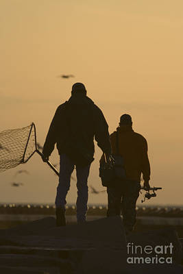 Fisherman Walking On Pier With Nets And Rods Against The Setting Sun Poster