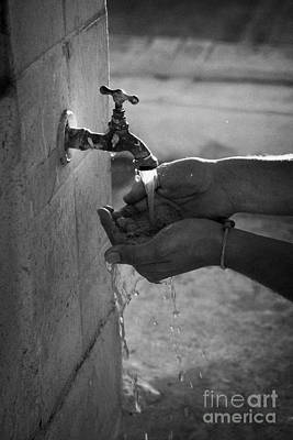 Hispanic Man Cupping Water And Washing Hands At Outdoor Tap Poster by Joe Fox