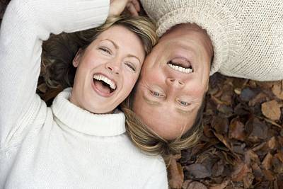 Laughing Couple Lying On Autumn Leaves Poster