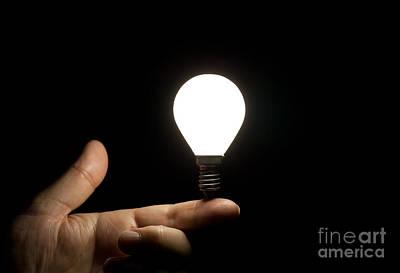 Lit Light Bulb Balancing On Finger Poster by Simon Bratt Photography LRPS