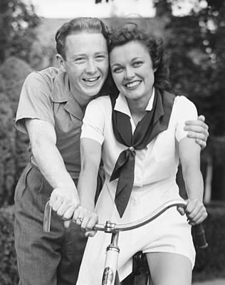 Man Embracing Woman Sitting On Bike, (b&w), Portrait Poster by George Marks