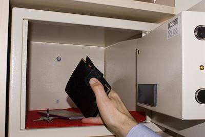 Man Taking Wallet From Hotel In-room Safe Poster by Mark Williamson