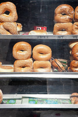 Selection Of Bagels On Shelves Behind A Shop Window Poster