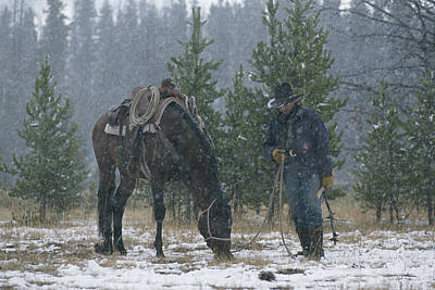 Snow Falls On A Cowboy And His Horse Poster by Annie Griffiths