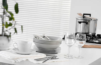 Stacked Dishes And Cutlery On Table Poster