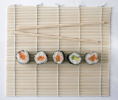 Sushi And Chopsticks On A Wooden Mat Poster by Larry Washburn