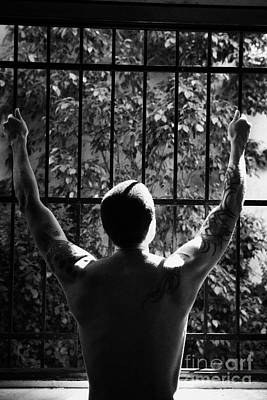 Tatooed Man Stretching Arms Out On Security Safety Cage Across Open Window Poster