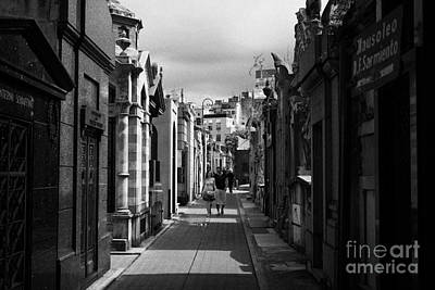 Tourists Walk Row Of Older Mausoleums On A Street In Recoleta Cemetery Capital Federal Buenos Aires Poster by Joe Fox