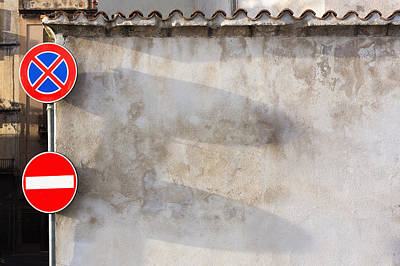 Two Traffic Signs On A Wall In The Town Poster