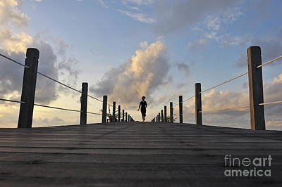 Woman Running On Wooden Jetty At Sunrise Poster by Sami Sarkis