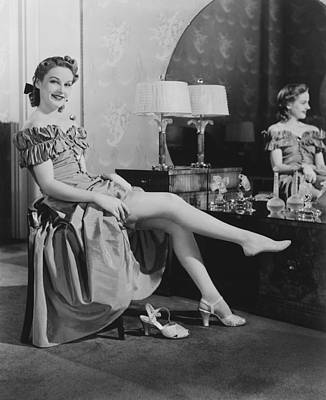 Woman Sitting At Vanity Table, Putting On Stockings, (b&w), Portrait Poster