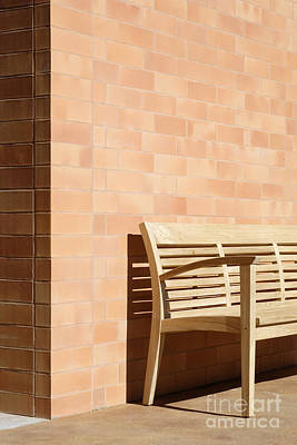 Wooden Bench Against Corner Of Brick Building Poster