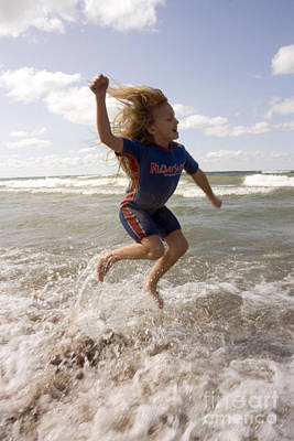 Young Girl Jumping Above Surf Poster by Christopher Purcell