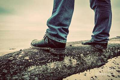 Man In Jeans And Elegant Shoes Standing On Fallen Tree On Wild Beach Looking At Sea Poster