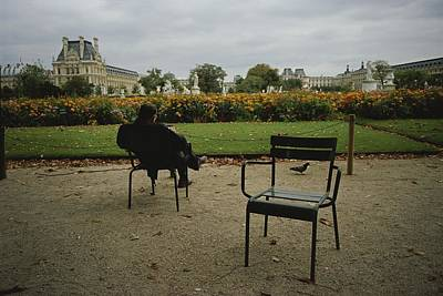 A Man Reads In The Tuileries Gardens Poster by Raul Touzon