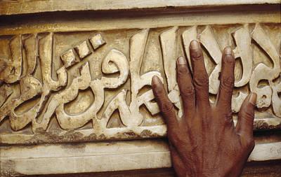 A Man Runs His Hand Over Arabic Script Poster by Justin Guariglia