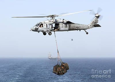 A Mh-60 Helicopter Transfers Cargo Poster by Gert Kromhout