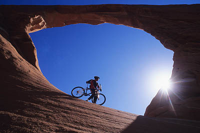 A Mountain Biker Stands Under An Arch Poster