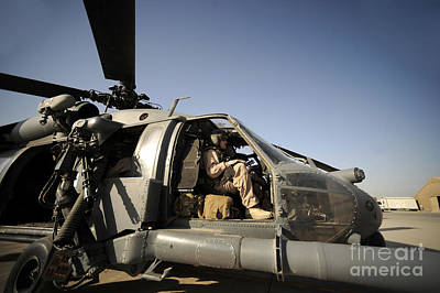 A Pilot Sits In The Cockpit Of A Hh-60g Poster