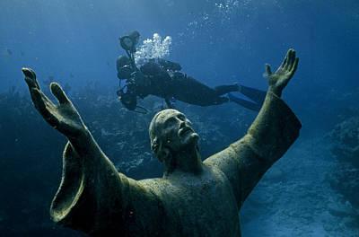 A Scuba Diver Swims Past The Statue Poster