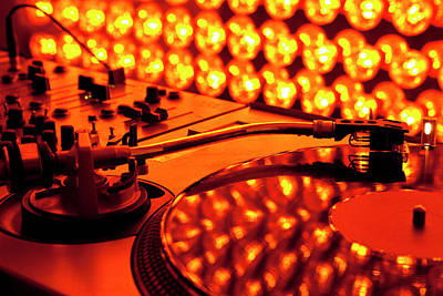 A Turntable And Sound Mixer Illuminated By Lighting Equipment Poster by Twins