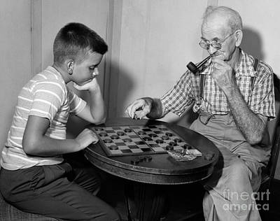 Boy Playing Checkers With Grandfather Poster by Debrocke/ClassicStock