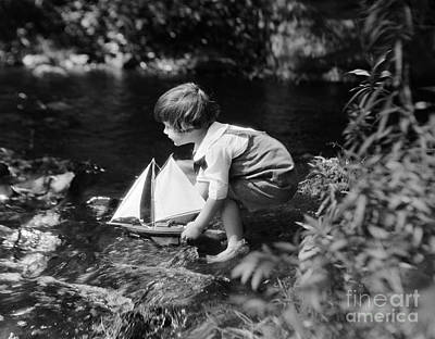 Boy Putting Toy Sailboat Into Stream Poster by H. Armstrong Roberts/ClassicStock