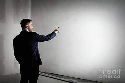 Businessman In An Open Empty Space Indoors Pointing His Finger At The Wall. Poster by Michal Bednarek