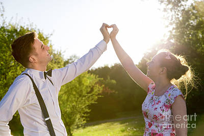 Couple In Love Making A Heart Shape With Their Hands In Sunshine Poster