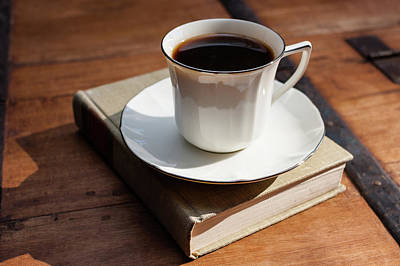Cup Of Coffee Upon A Closed Book On Wooden Table Poster by Bradley Hebdon