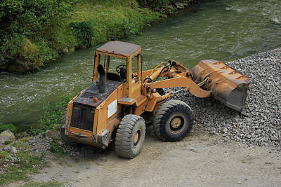 Front End Loader Next To A River Poster