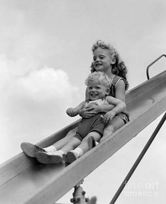 Girl And Little Boy Going Down Slide Poster