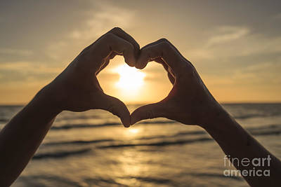 Hands Forming Heart Around Sunset Poster