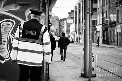 irish garda police sergeant on foot patrol in dublin city centre Ireland Poster by Joe Fox