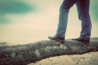 Man In Jeans And Elegant Shoes Standing On Fallen Tree On Wild Beach Looking At Sea. Vintage Poster