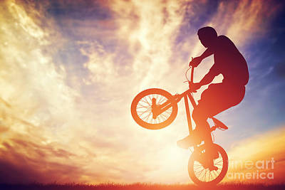 Man Riding A Bmx Bike Performing A Trick Against Sunset Sky Poster