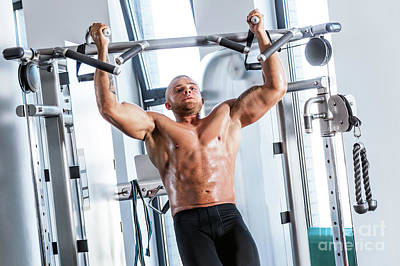Muscular Strong Man Working Out At A Gym. Poster