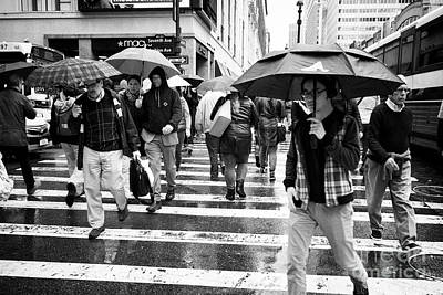 people holding umbrellas cross a wet city street during rain shower midtown New York City USA Poster