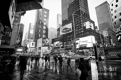 people holding umbrellas walk through wet times square during rain shower midtown New York City USA Poster