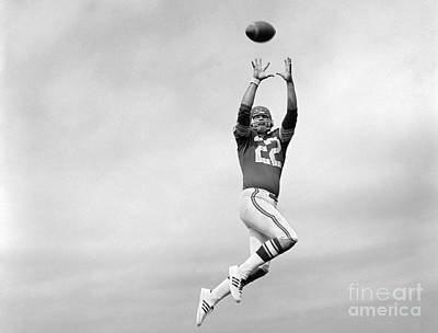 Player Jumping To Catch Football Poster