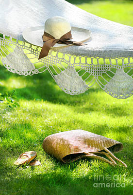 Straw Hat With Brown Ribbon Laying On Hammock Poster