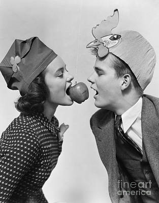 Teen Girl And Boy Bobbing For Apple Poster