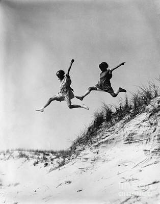 Two Girls Leaping Off Sand Dune Poster by H. Armstrong Roberts/ClassicStock