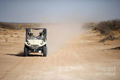 U.s. Soldiers Drive A Ltatv Down A Dirt Poster