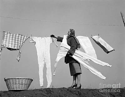 Woman Removing Frozen Clothes Poster by Debrocke/ClassicStock